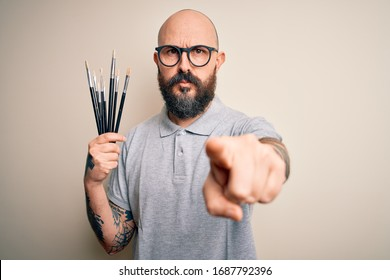 Handsome bald artist man with beard and tattoo painting using painter brushes pointing with finger to the camera and to you, hand sign, positive and confident gesture from the front