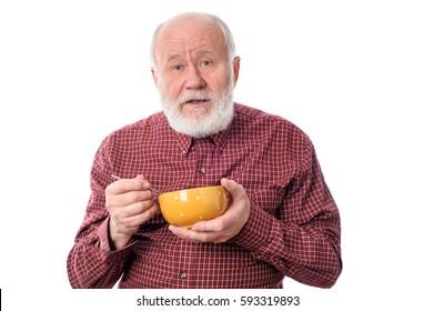 Handsome bald and bearded senior man eating something from orange ceramic bowl, isolated on white background