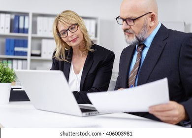 Handsome bald businessman with beard and eyeglasses discussing something at desk in front of computer in office
