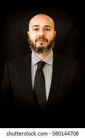 Handsome, bald man with beard,  in suit and tie,  on black background