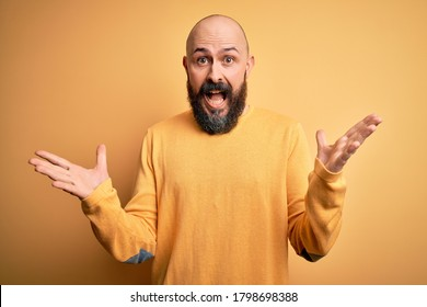 Handsome bald man with beard wearing casual sweater standing over yellow background celebrating crazy and amazed for success with arms raised and open eyes screaming excited. Winner concept