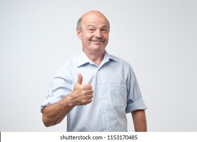 Handsome, bald man in blue shirt with his thumb up in sign of optimism on white background. Success in business or in personal life