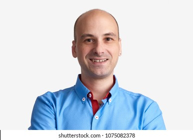 Handsome bald man looking at camera isolated on grey background. Portrait of laughing guy smiling