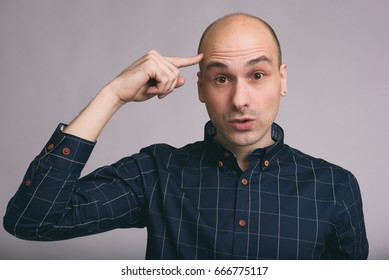 Handsome bald man thinking with finger on head over gray background