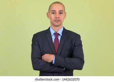 Handsome bald multi ethnic businessman with arms crossed