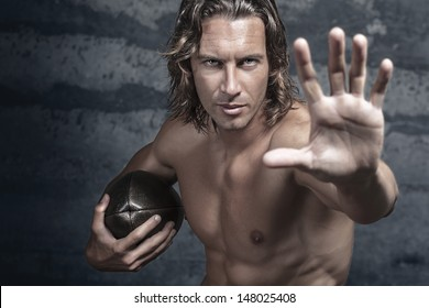 handsome bare chested muscle model is opening his hand in halt gesture and holds football ball