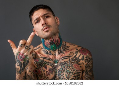 Handsome bare-chested tattooed man making middle finger gesture