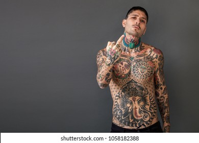 Handsome bare-chested tattooed man portrait giving the middle finger