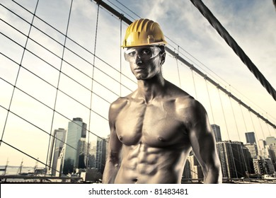 Handsome bare-chested worker with cityscape in the background