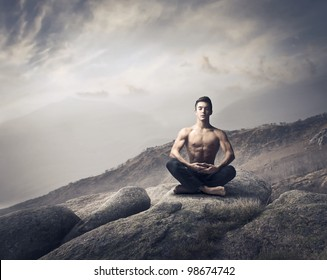 Handsome bare-chested young man doing yoga on a rock