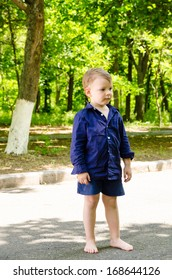 Handsome barefoot little boy standing waiting in the middle of a leafy rural road watching and waiting looking off to the right of the frame