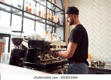 Handsome barista with beard making cappuccino on coffee machine