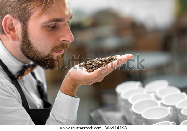 Handsome barista in classical uniform checking coffee beans at the cafe terrace