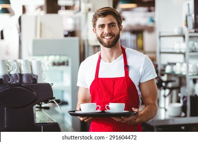 Handsome barista holding two cups of coffee in the cafe