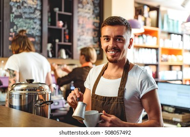 handsome barista making a beverage and looking into a camera