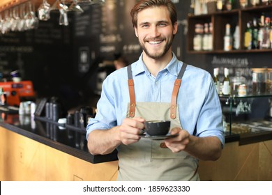 Handsome barista offering a cup of coffee to camera at the coffee shop.