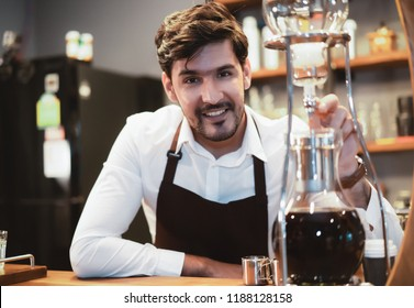 Handsome barista preparing drip coffee for customer in coffee shop and looking at camera.Startup Small business concept. Hipster barista man with beard.