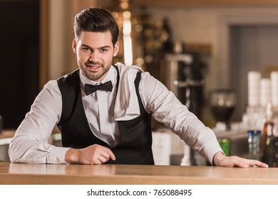 handsome barman leaning on bar counter and looking at the camera
