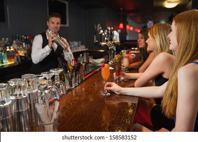 Handsome bartender making cocktails for attractive women in a classy bar