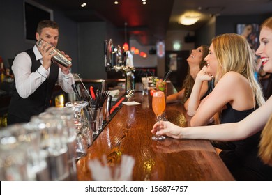 Handsome bartender making cocktails for beautiful women in a classy bar