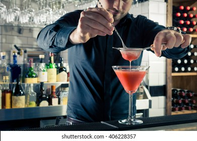 Handsome bartender mixologist decorating strawberry martini style cocktail in bar black shirt stylish