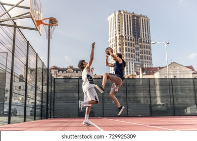 Handsome basketball players are playing on basketball court outdoors