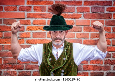 handsome bavarian man flexing his muscles in front of brick wall