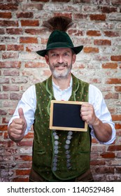 handsome bavarian man holding a black board and thumbs up
