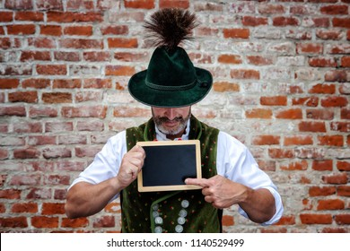 handsome bavarian man holding a black board