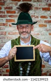 handsome bavarian man holding a black board
