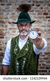 handsome bavarian man holding a clock towards camera