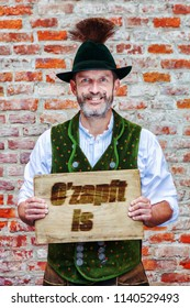 handsome bavarian man holding a sign with german words for Beer Is Flowing Now