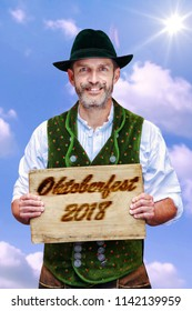 handsome bavarian man holding a sign with the words Oktoberfest 2018