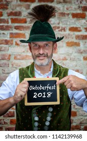 handsome bavarian man holding sign with the words Oktoberfest 2018