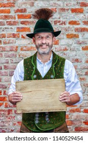 handsome bavarian man holding a wooden plank in his hands