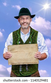 handsome bavarian man standing under blue sky and holding wooden plank