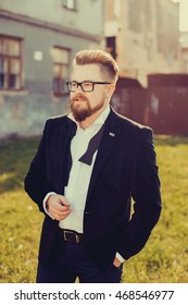 handsome beard man posing in the street, outdoor portrait, glasses, fashion model