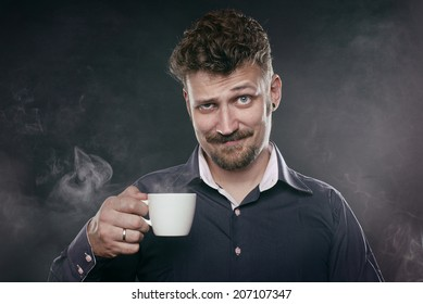 handsome beard man stand in fog with cup of coffee in his hand and look at camera