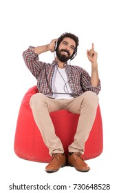 Handsome beard man wearing caro shirt and beige pants, guy sitting on red chair and listening to music, isolated on white background