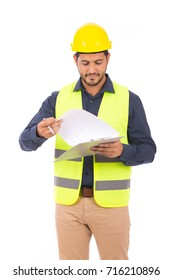 Handsome beard young engineer holding a clipboard and reading some notes, guy wearing blue shirt and beige pants with a yellow vest and yellow helmet, isolated on white background