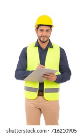 Handsome beard young engineer smiling and holding a clipboard, guy wearing blue shirt and beige pants with a yellow vest and yellow helmet, isolated on white background