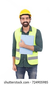 Handsome beard young engineer smiling and holding a clipboard, guy wearing green shirt and jeans with a yellow vest and yellow helmet, isolated on white background