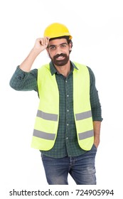 Handsome beard young engineer smiling and holding his helmet, guy wearing green shirt and jeans with a yellow vest, isolated on white background