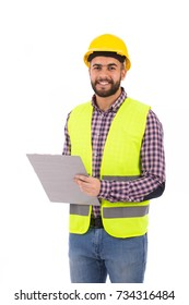 Handsome beard young engineer smiling and holding a clipboard, guy wearing caro shirt and jeans with a yellow vest and yellow helmet, isolated on white background