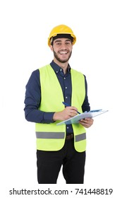 Handsome beard young engineer smiling and holding a clipboard, guy wearing blue shirt and black pants with a yellow vest and yellow helmet, isolated on white background