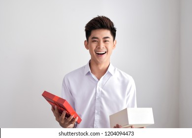 Handsome beard young man smiling and opening a brown gift box, guy wearing white shirt, isolated on white background
