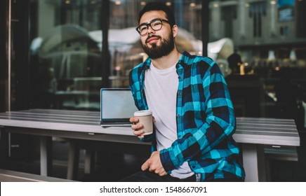 Handsome bearded 20s student in eyewear looking away dreaming about smth during coffee break in cafe outdoors, pondering asian hipster guy freelancer having break working remotely on laptop
