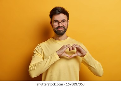 Handsome bearded adult man holds hands in shape of heart, expresses his affection to girlfriend, adores someone, says be my valentine, dressed in near sweater, isolated on yellow background.