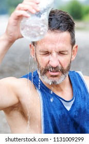 handsome bearded athlete standing outdoors and pouring water on himself