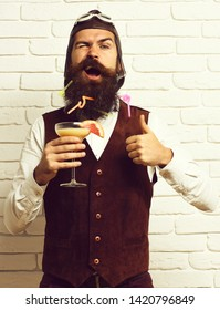 handsome bearded aviator man with long beard and mustache on funny face holding glass of alcoholic cocktail in vintage suede leather waistcoat with hat and glasses on white brick wall background.